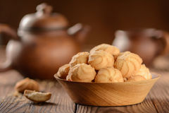 Cookies in a wooden plate with a clay teapot and a cup on a wooden table Royalty Free Stock Images