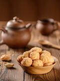 Cookies in a wooden plate with a clay teapot and a cup on a wooden table Stock Photo