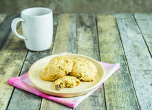 Cookies in wooden plate and coffee cup on wooden background Royalty Free Stock Photography