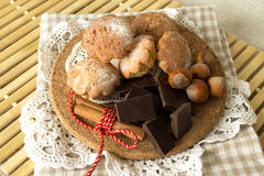 Cookies on a wooden plate. Homemade cakes, chocolate and nuts on a wooden stand and lacy napkin Royalty Free Stock Photos