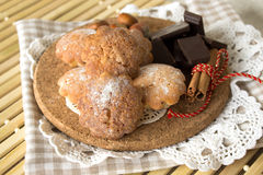 Cookies on a wooden plate. Homemade cakes, chocolate and nuts on a wooden stand and lacy napkin Stock Photos
