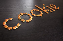 Cookies. Word cookie composed of cookies on a black wood background Stock Photos