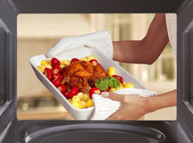 Cooking. Hands of woman is taking out chicken with potato from oven royalty free stock images