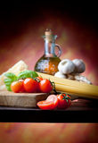 Cooking. Raw pasta with tomato, basill, garlic, Parmesan cheese and olive oil close up Royalty Free Stock Photos