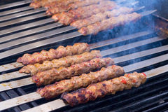 Cooking Adana Lamb Kebabs on the Restaurant Style Grill. Cooking Adana kebabs on the restaurant style grill, smoke  coming out from them that they might be ready Royalty Free Stock Image