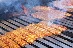 Cooking Adana Lamb Kebabs on the Restaurant Style Grill. Cooking Adana kebabs on the restaurant style grill, smoke  coming out from them that they might be ready Stock Image
