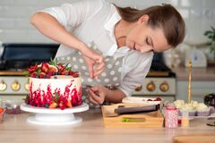 Free Cooking And Decoration Of Cake With Cream. Young Woman Pastry Chef In The Kitchen Decorating Red Velvet Cake Stock Photography - 197948932