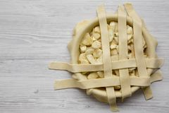 Cooking apple pie on a white wooden background, top view. Copy space.  royalty free stock image