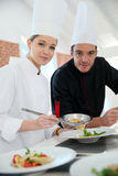 Cooking apprentice with the chef Stock Images