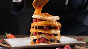 Cooking art. Chef spreading caramel on top of stack of fresh fluffy pancakes decorated with forest berries. Homemade. Healthy Vegan Fluffy American Style stock video