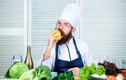 Cooking as hobby and professional occupation. Colorful culinary. Vegetarian diet concept. Chef cooking sweet pepper. Man. Wear apron cooking in kitchen. Man royalty free stock photos