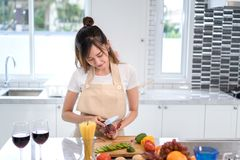 Cooking asian woman housewife in the kitchen making healthy food. With vegetables diet dinner at home Royalty Free Stock Images