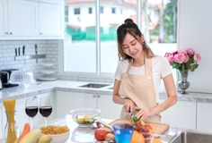 Cooking asian woman housewife in the kitchen making healthy food. With vegetables diet dinner at home Stock Photo