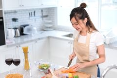 Cooking asian woman housewife in the kitchen making healthy food. With vegetables diet dinner at home Royalty Free Stock Photo