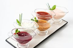 Cooking assortment gravy boat sauce composition. Cooking assortment. Creative sauce composition. Glass gravy boats on white platter stock photos