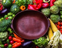 Cooking autumn harvest background concept. Fresh organic vegetables around empty clay pot. Organic vegetarian vegan ingredients for cooking. Healthy clean Stock Photo