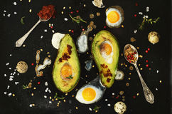 Cooking avocado with quail eggs and spices Royalty Free Stock Images