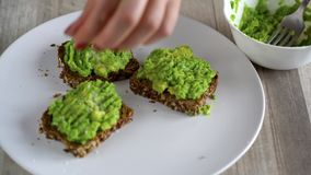 Spreading mashed avocado on toast and sprinkle with salt and spices. Healthy vegan breakfast. stock video