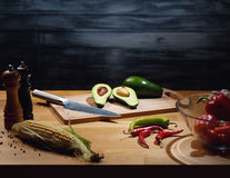 Cooking background with avocado. Halved and whole ripe avocados on wooden board with knife. Low key shot, light on board, some vegetables around on table. Copy Royalty Free Stock Images