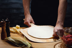 Cooking background with blank pizza base. Chef cooking pizza, putting blank pizza base on board. Low key shot, close up of hands, some ingredients around on royalty free stock photography