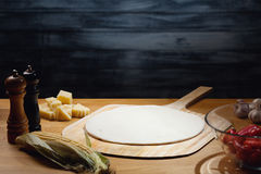 Cooking background with blank pizza base. Cooking pizza background, dough base on board. Low key shot, light on dough, some ingredients around on table. Copy royalty free stock image