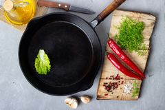 Cooking background concept - empty iron pan, cutting board and spices on a gray stone background royalty free stock photo