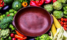 Cooking background concept. Fresh organic vegetables around empty clay pot. Organic vegetarian vegan ingredients for cooking. Healthy clean eating or harvest Royalty Free Stock Photography