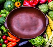 Cooking background concept. Fresh organic vegetables around empty clay pot. Organic vegetarian vegan ingredients for cooking. Healthy clean eating or harvest Royalty Free Stock Photo