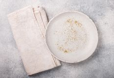 Cooking background with empty light plate and linen napkin on grey concrete table. Rustic style. Selective focus. Top view, copy space stock images