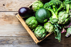 Cooking background harvest concept. Fresh organic green vegetables in wooden box. Cooking background harvest concept. Fresh organic green vegetables in clay pot Royalty Free Stock Image