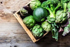 Cooking background harvest concept. Fresh organic green vegetables in wooden box. Cooking background harvest concept. Fresh organic green vegetables in clay pot Royalty Free Stock Photo