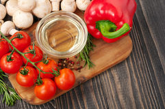 Cooking background - oil, mushrooms, cherry tomatoes, pepper and Royalty Free Stock Images