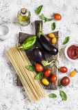Cooking background. Raw ingredients for making pasta - spaghetti, eggplant, tomatoes, pepper, olive oil, tomato sauce and basil on Royalty Free Stock Photo