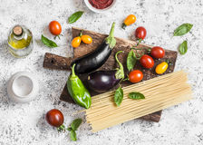 Cooking background. Raw ingredients for making pasta - spaghetti, eggplant, tomatoes, pepper, olive oil, tomato sauce and basil on Stock Photo