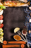 Cooking background. Smoked fish with spices, fruits and lemon on Stock Images