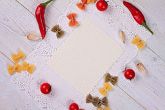 Cooking background. Tomatos, red pepper and Farfalle Pasta and blank paper for copy space on white rustic wooden table. Italian cu Royalty Free Stock Photo