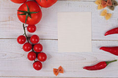 Cooking background. Tomatos, red pepper and Farfalle Pasta and blank paper for copy space on white rustic wooden table. Italian cu Stock Photos