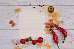 Cooking background. Tomatos, red pepper and Farfalle Pasta and blank paper on white rustic wooden table. Italian cuisine Recipe Pl Royalty Free Stock Images