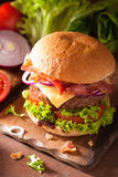 Cooking bacon cheese burger with beef patty tomato onion Royalty Free Stock Photo