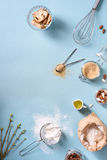 Cooking and baking ingredients - egg, flour, brown sugar, almonds over blue table. Spring theme. Top view, copy space,. Flat lay Stock Photo