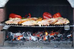 Cooking in the barbecue. A delicious meal in the barbecue. Peppers and chicken roasted in the barbecue. Summer meal. Stock Photography