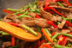 Cooking beef, capsicum and bean stirfry in wok Stock Photography