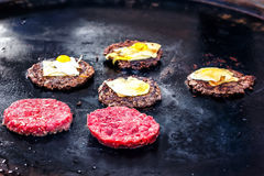 Cooking beef and pork patty with eggs and cheese for burger. Meat roasted on fire barbecue kebabs on the grill. Royalty Free Stock Photo