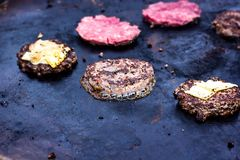 Cooking beef and pork patty with eggs and cheese for burger. Meat roasted on fire barbecue kebabs on the grill. Grilled burger cut. Let beef minced meat patties Royalty Free Stock Images