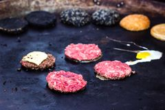 Cooking beef and pork patty with eggs and cheese for burger. Meat roasted on fire barbecue kebabs on the grill. Grilled burger cut. Let beef minced meat patties Royalty Free Stock Photography