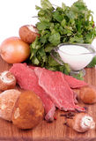 Cooking Beef Stroganoff. Arrangement of Ingredients with Raw Beef, Fresh Porcini Mushrooms, Onion, Spices, Greens and Milk closeup on Wooden Cutting Board Royalty Free Stock Image