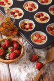 Cooking berry muffins with fresh strawberries, vertical Stock Photo