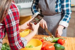 Cooking blog women cutting vegetables smartphone stock images