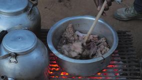 Hand Raises The Lid Of The Pan And Stir The Chicken With A Spoon. Cooking and boiling grilled water with hot coals in hungry Africa. Hand raises the lid of the stock video footage