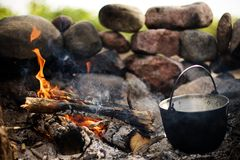 Cooking on the bonfire. Campfire with charcoal, stones and kitchenware royalty free stock images